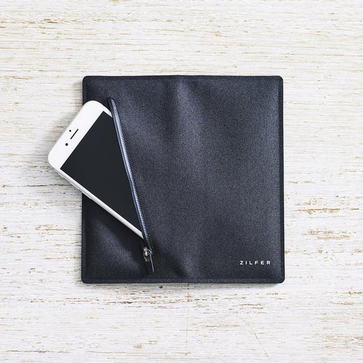 Zilfer Phone Wallet In Black Open Rear With White iPhone Going Into Pocket On Light Wood Desk