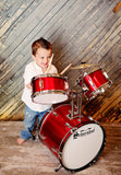 Child playing Schoenhut 5-Piece Drum Set Red