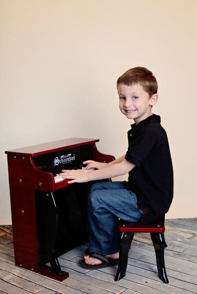 Boy playing Schoenhut Elite Spinet Piano 25-Key Mahogany/Black
