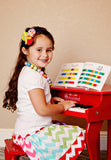 Girl playing Schoenhut Fancy Baby Grand Piano 30-Key Red