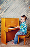 Boy playing Schoenhut Day Care Durable Piano 37-Key Oak