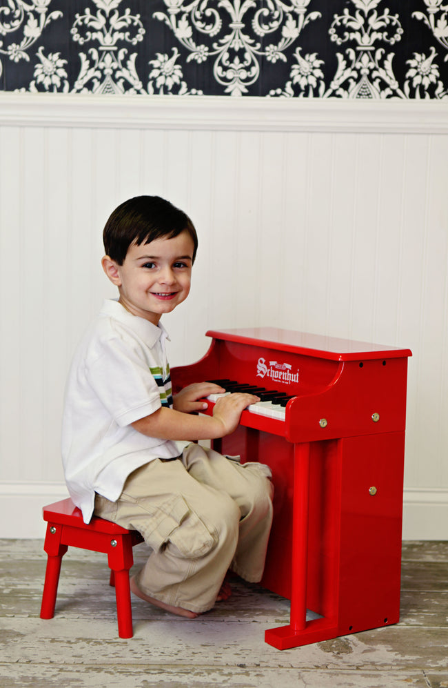 Child with Schoenhut Traditional Spinet Piano 25-Key Red