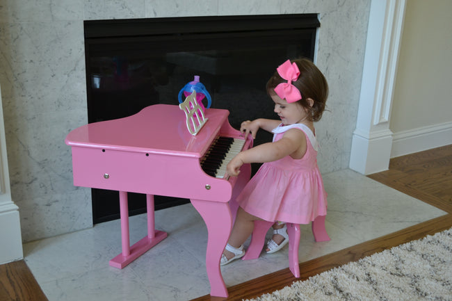 Girl playing Schoenhut Fancy Baby Grand Piano 30-Key Pink