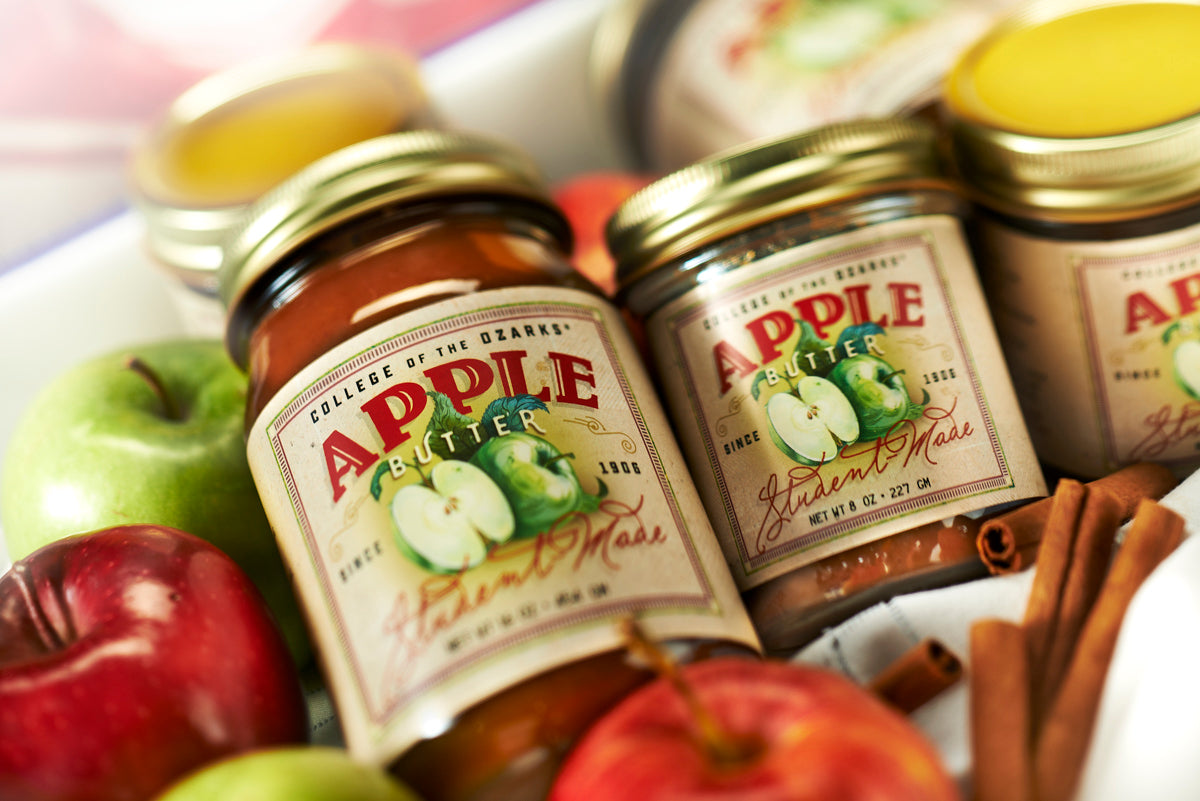 Close up of green and red apples, cinnamon sticks and jars of student-made apple butter on a table