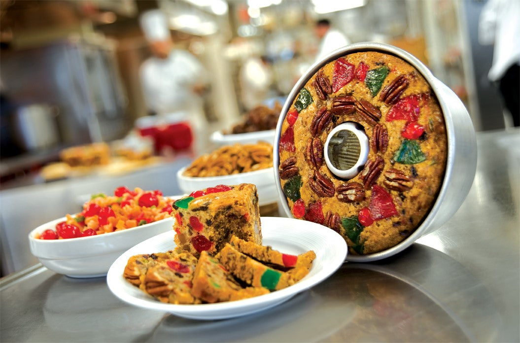 One whole fruitcake in tin and a plate of fruitcake slices sit on top of a metal table in a kitchen
