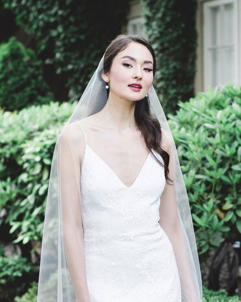Model wearing pearl, floral and crystal bridal earrings and long tulle veil
