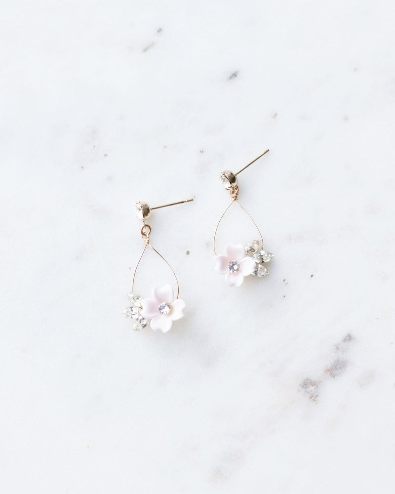 Flat lay photo of the Belle Fleur Earrings in rose gold, blush flowers, crystal. Delicate statement bridal earrings.