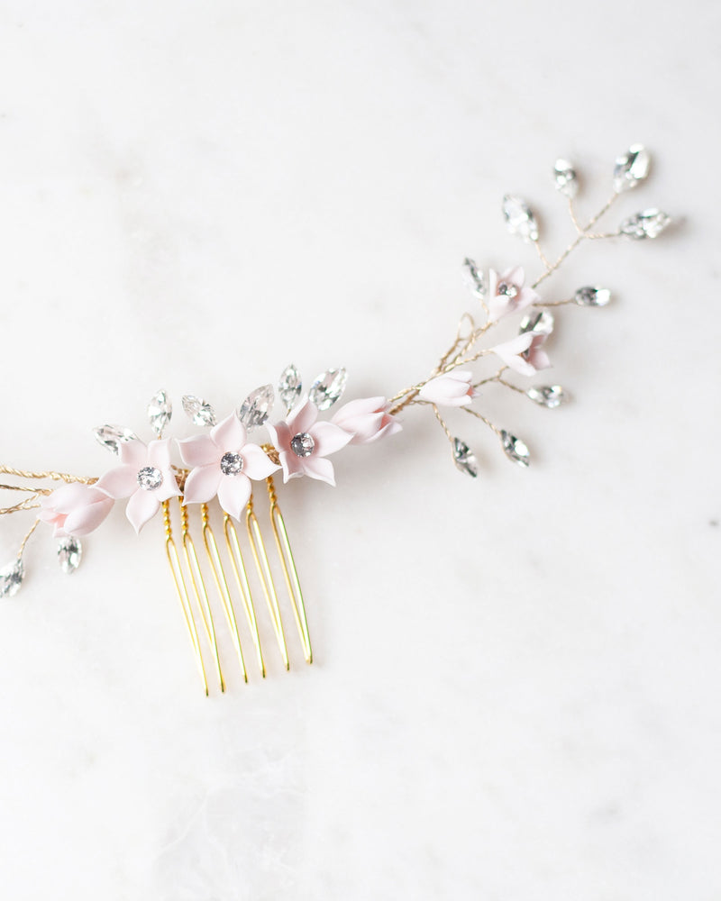 A close up of the Belle Fleur Grand hair Comb in gold by Atelier Elise, made of delicate flowers, swarovski crystals, and freshwater pearls.