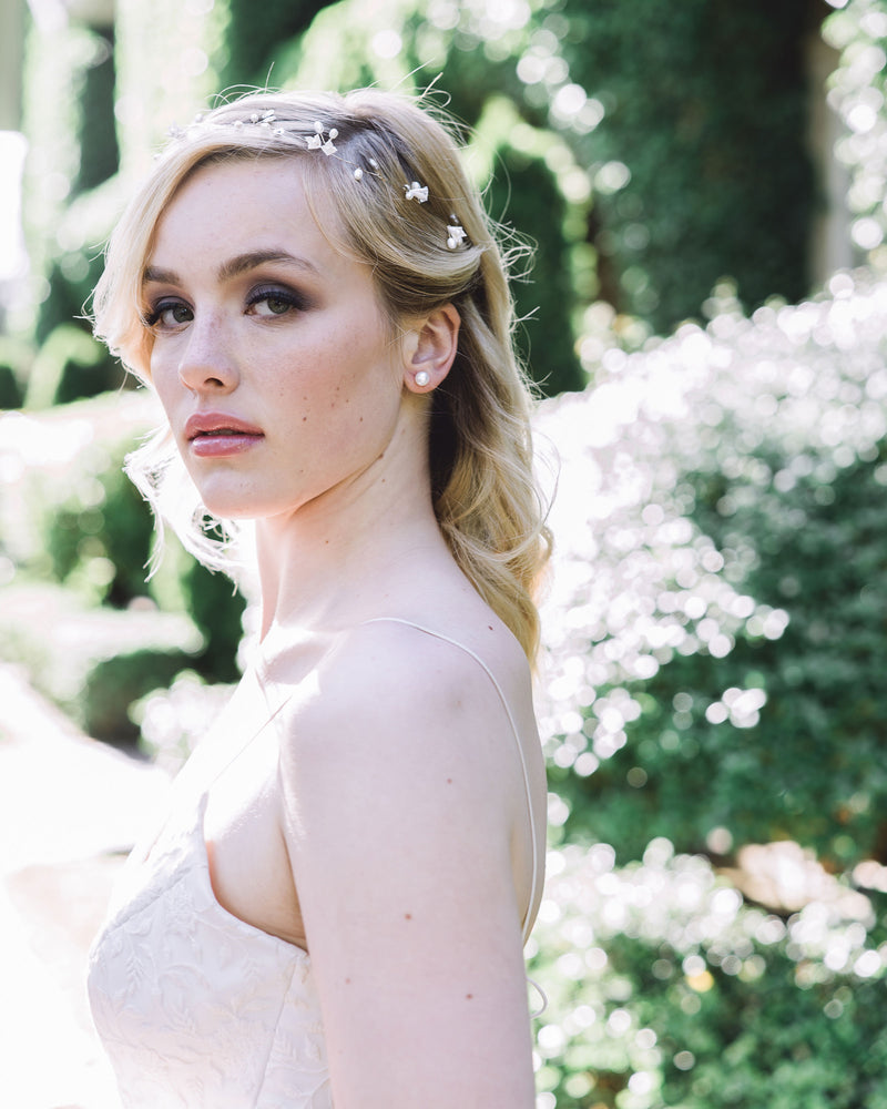 Model wearing the delicate Belle Fleur Hair Vine made of dainty flowers, pearls, and Swarovski crystals; styled to front with tiny pearl studs.