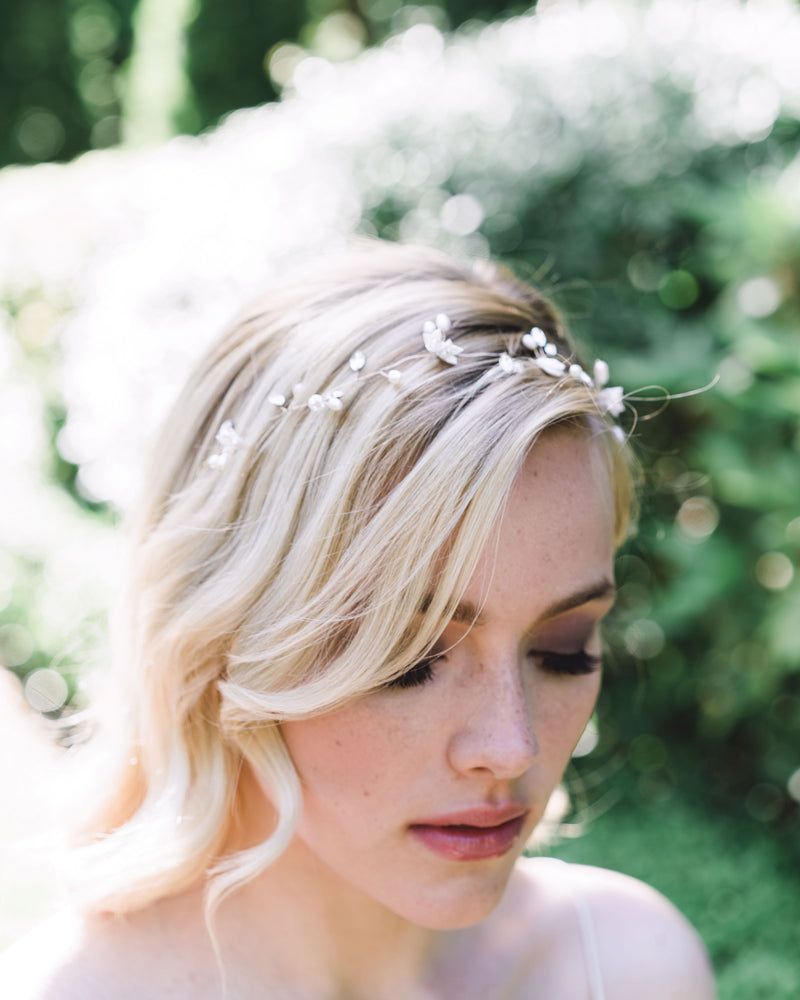 Model wearing the delicate Belle Fleur Hair Vine made of dainty flowers, pearls, and Swarovski crystals; styled to front with flowing waves.