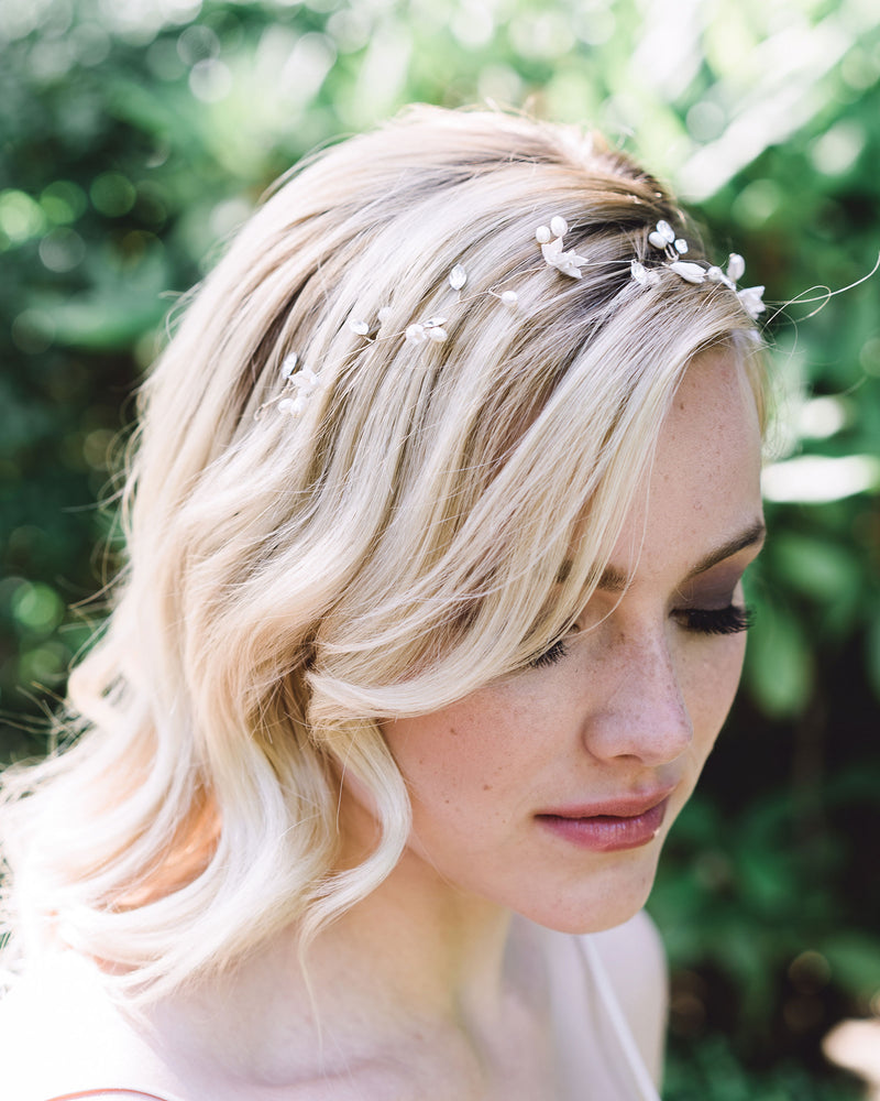 Model wearing the delicate Belle Fleur bridal Hair Vine in gold made of dainty flowers, pearls, and Swarovski crystals; styled to front with waves