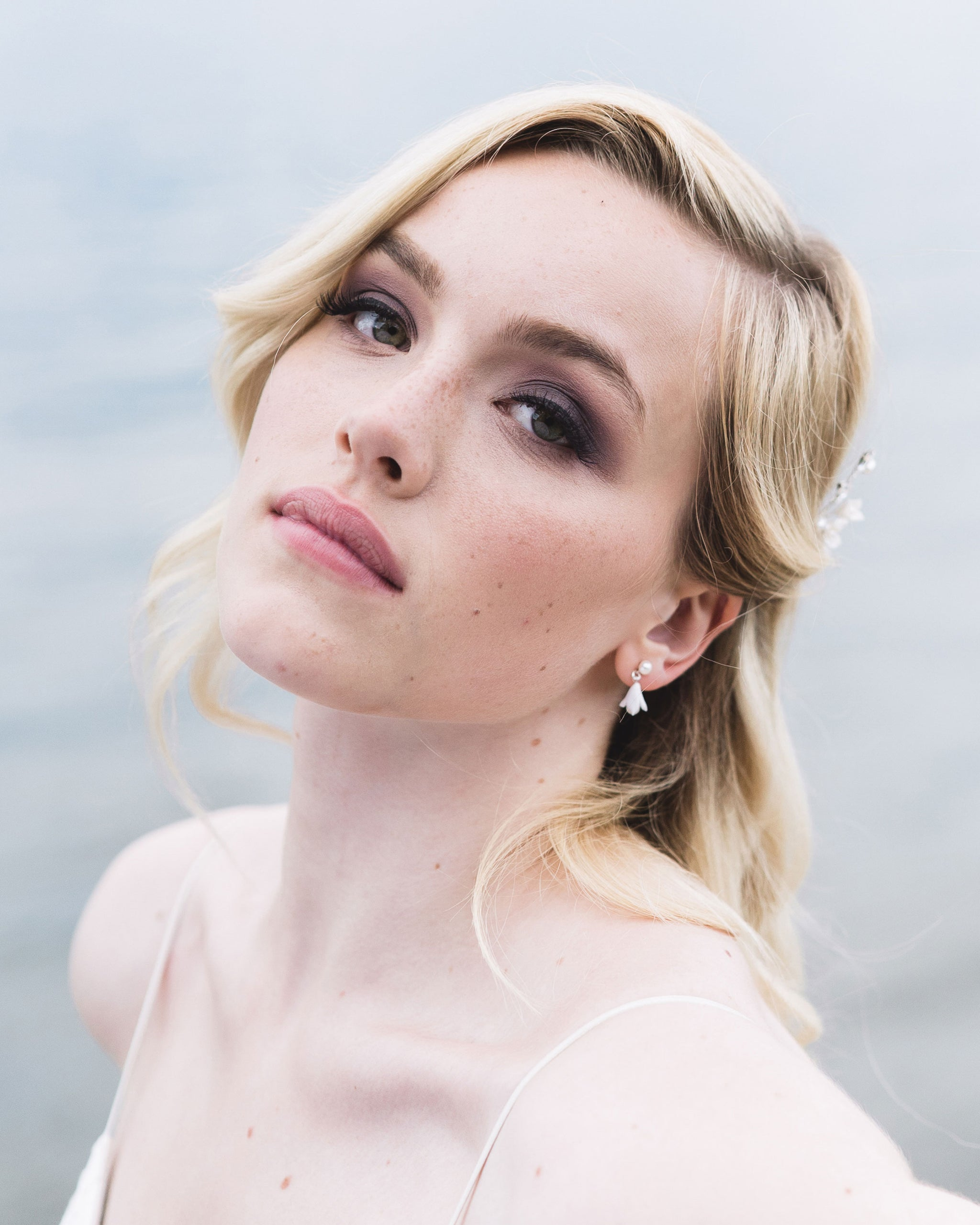 Model wearing delicate drop bridal earrings with freshwater pearls and dainty clay flowers.