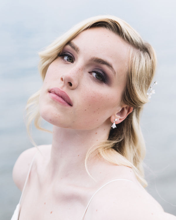 Model wearing belle fleur petite earrings delicate drop bridal earrings with freshwater pearls and dainty clay flowers.