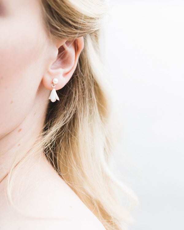 Close up on model of the Belle Fleur Petite Earrings; delicate drop wedding earrings with pearls and clay flowers