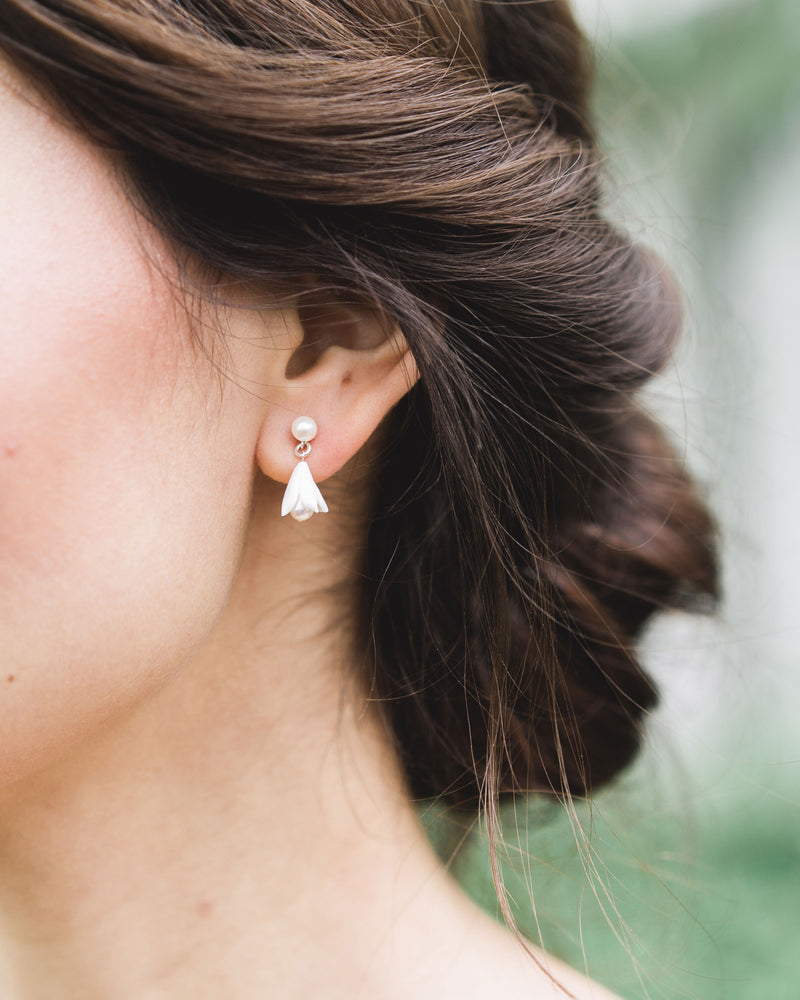 Close up of model with low bun updo and drop Earrings; Belle fleur small drop bridal earrings with pearls and clay flowers