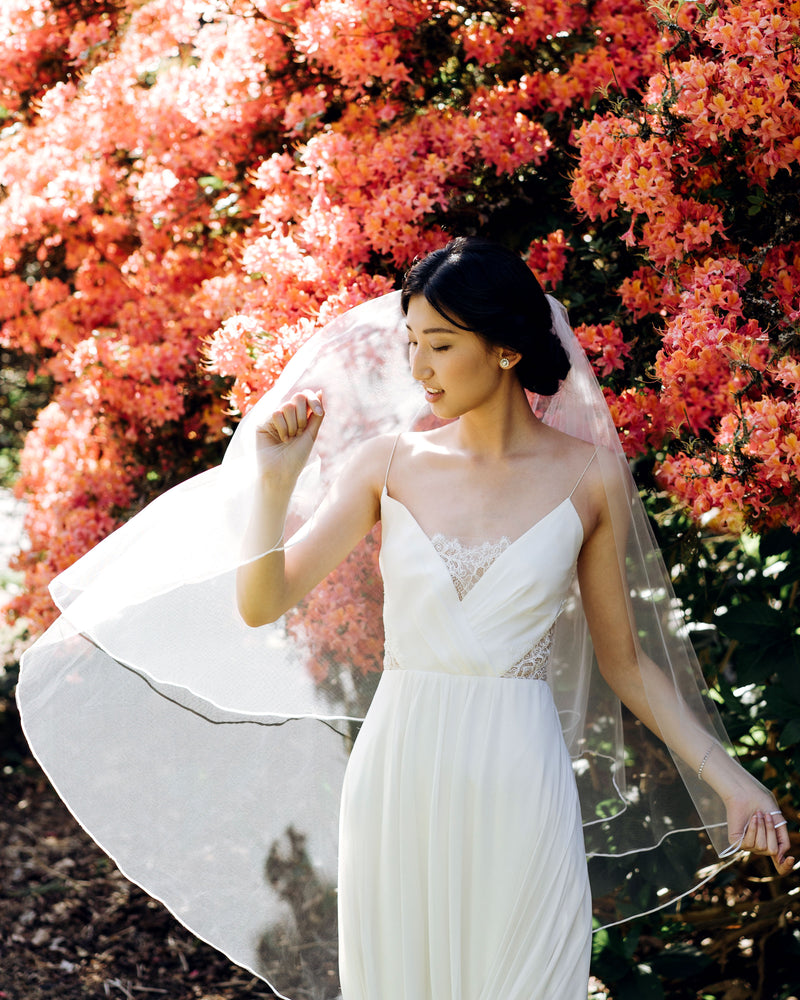 Model wearing calla wedding veil with ribbon edging