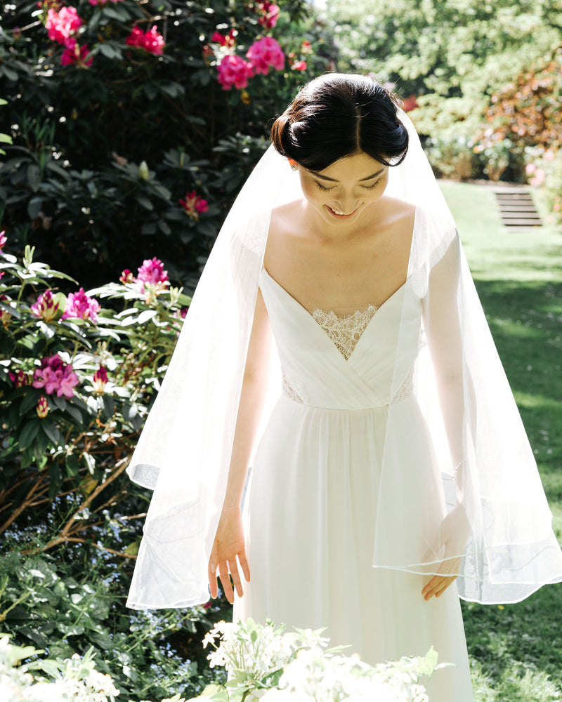 Model wearing calla fingertip short bridal veil with ribbon edge