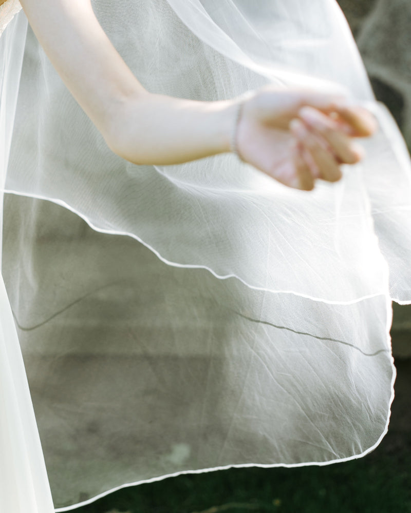 Details of the calla fingertip veil with ribbon edging and blusher