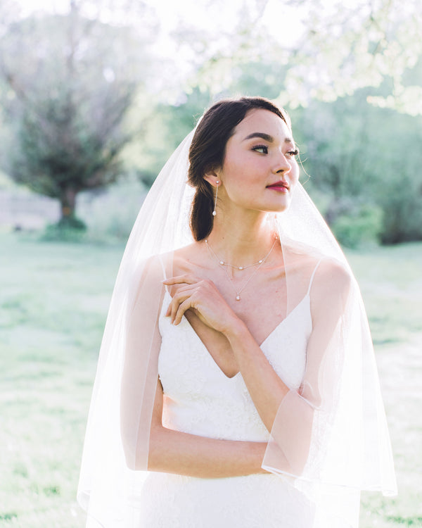 Model wearing calla chapel bridal veil with ribbon edge