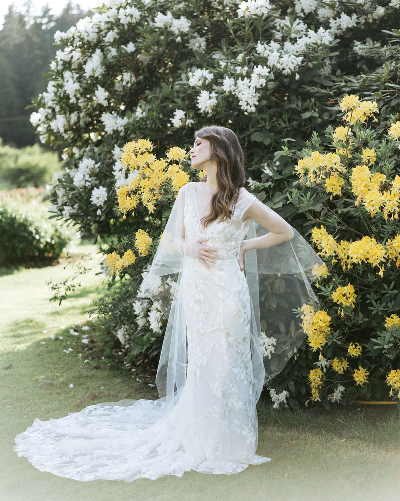 model wearing cascading leaves tulle bridal cape veil