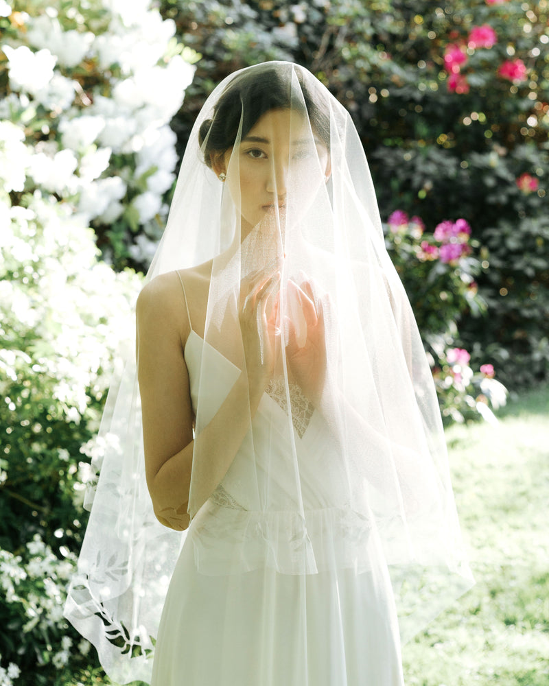 Model wearing cascading leaves tulle wedding veil