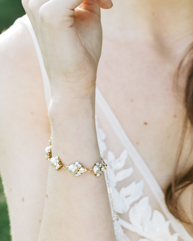 Model wearing celestial swarovski crystal pearl bracelet in gold wedding jewellery