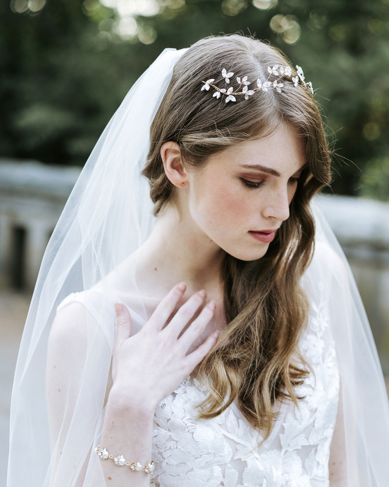 Model wearing celestial swarovski crystal pearl bracelet in gold wedding jewelry