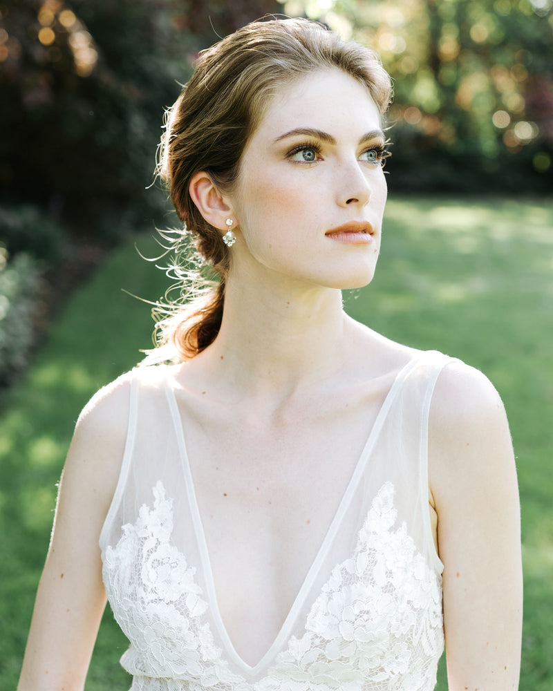 model wearing celestial silver pearl drop earrings in gold with white freshwater pearl and swarovski crystals bridal jewelry