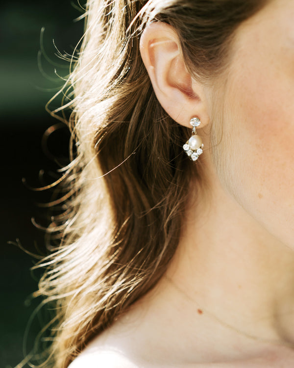 model wearing celestial silver pearl drop earrings in gold with white freshwater pearl and swarovski crystals bridal jewellery