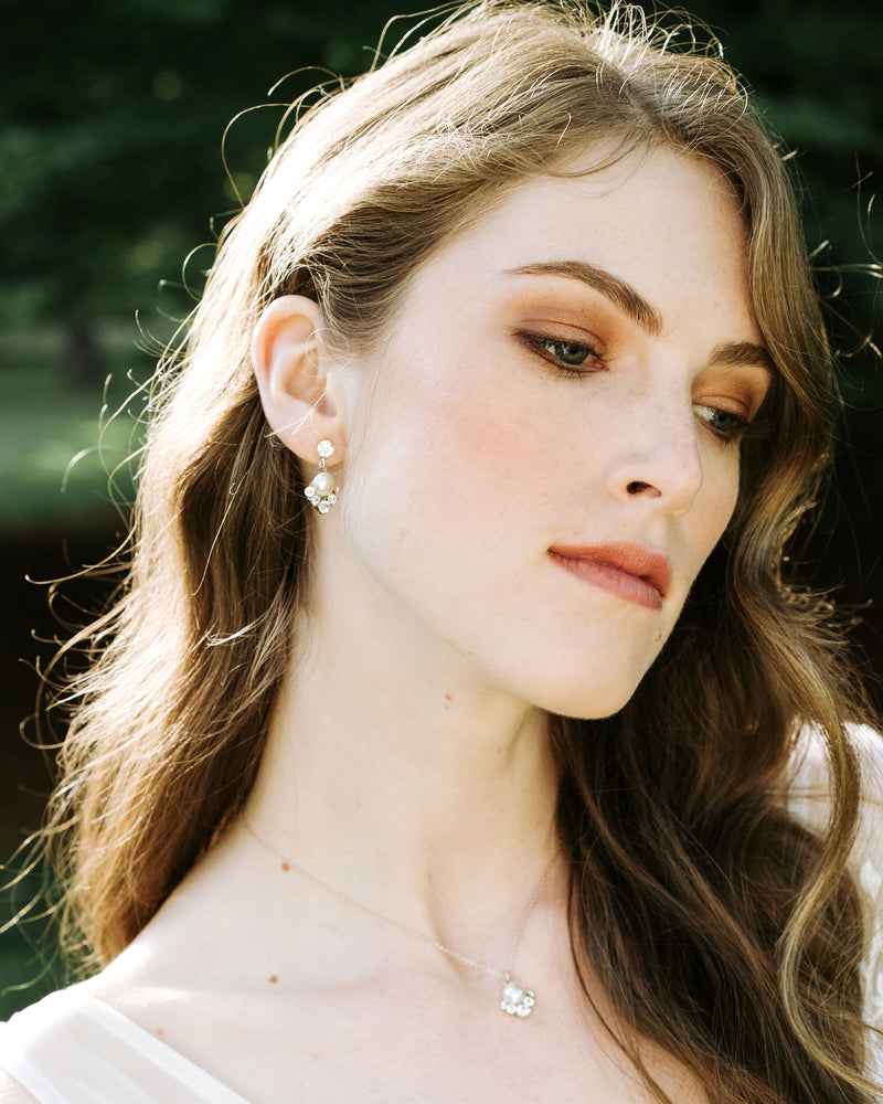 model wearing celestial silver pearl drop earrings in gold with white freshwater pearl and swarovski crystals wedding jewellery
