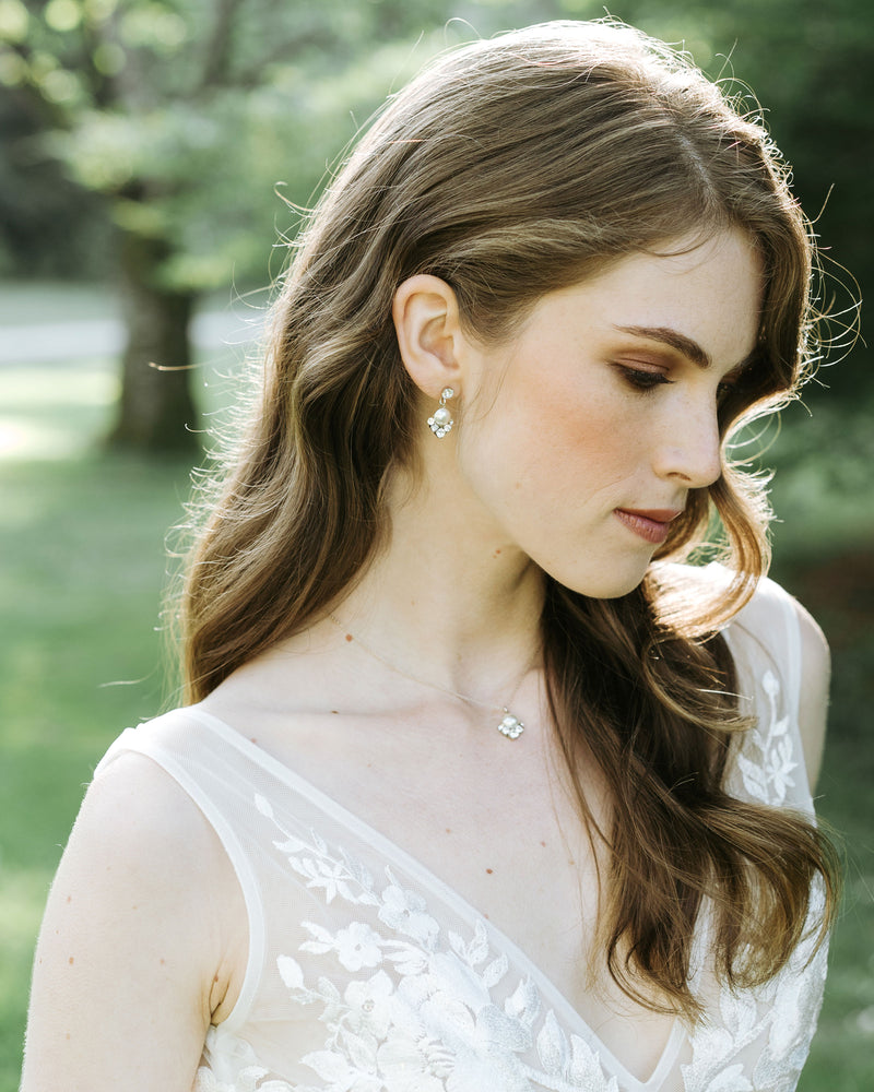 model wearing celestial silver pearl drop earrings in gold with white freshwater pearl and swarovski crystals wedding jewelry