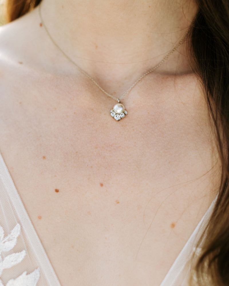 model wearing celestial drop necklace in silver with cream freshwater pearl and swarovski crystals bridal jewelry