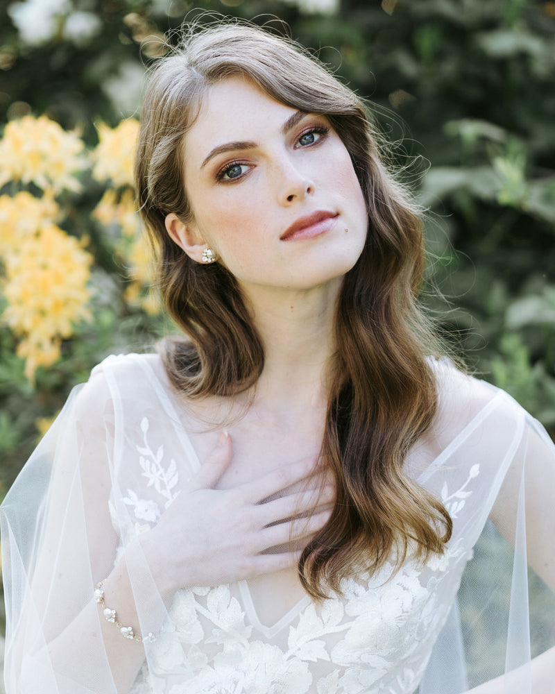 model wearing celestial pearl stud earrings in gold with white freshwater pearl and swarovski crystals bridal jewelry