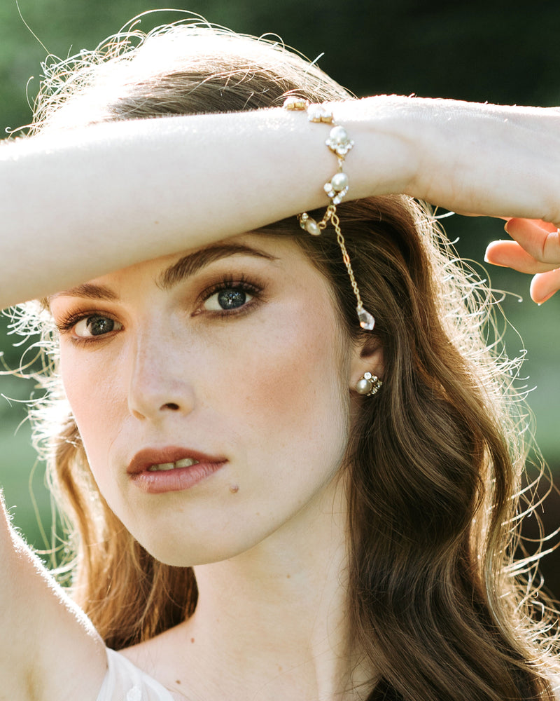 model wearing celestial pearl stud earrings in gold with white freshwater pearl and swarovski crystals wedding jewelry set