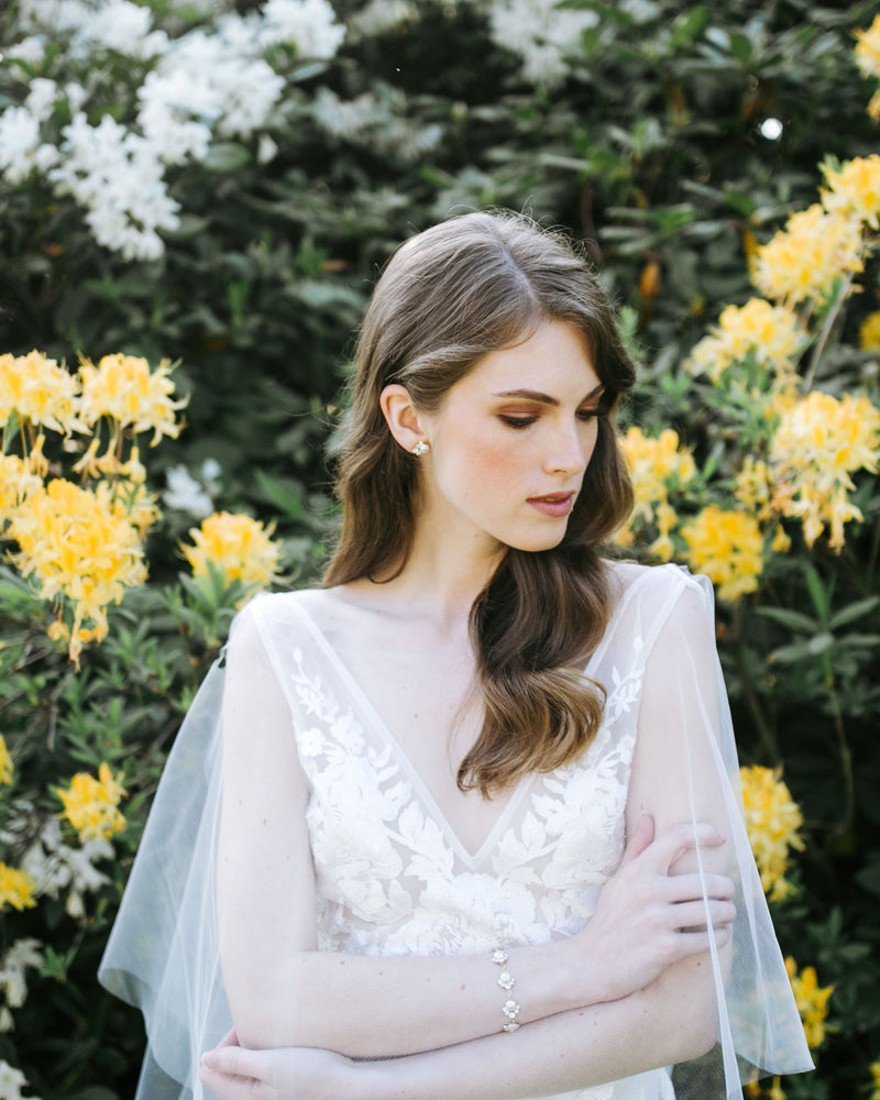 model wearing celestial pearl stud earrings in gold with white freshwater pearl and swarovski crystals wedding jewelry