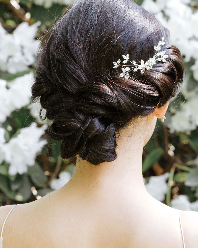 model wearing swarovski crystal blossoms petite delicate bridal comb in silver braid low bun