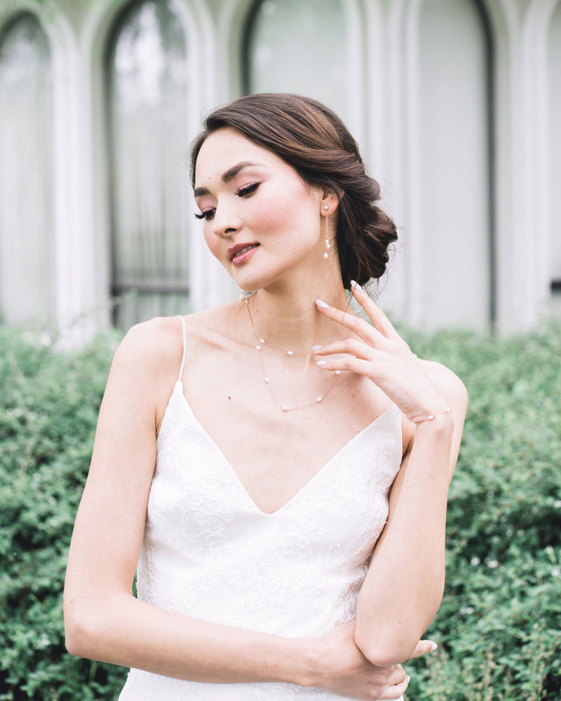 model wearing dainty freshwater pearl bracelet in gold bridal matching set
