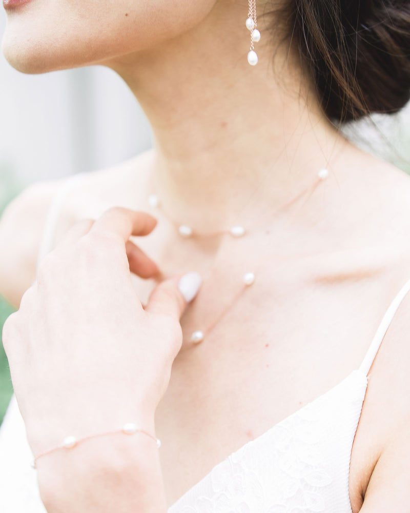 model wearing dainty freshwater pearl bracelet in gold with matching neckace bridal jewelry set