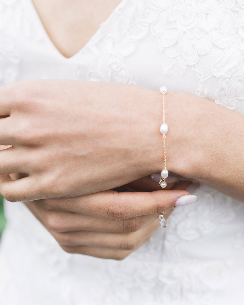 model wearing dainty freshwater pearl bracelet in gold