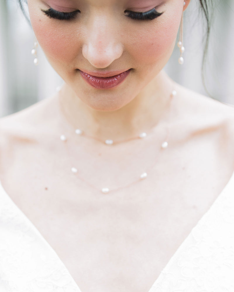 A close up of a model wearing our Dainty Pearl Layered Necklace in rose gold with matching Dainty Pearl Trio Earrings.