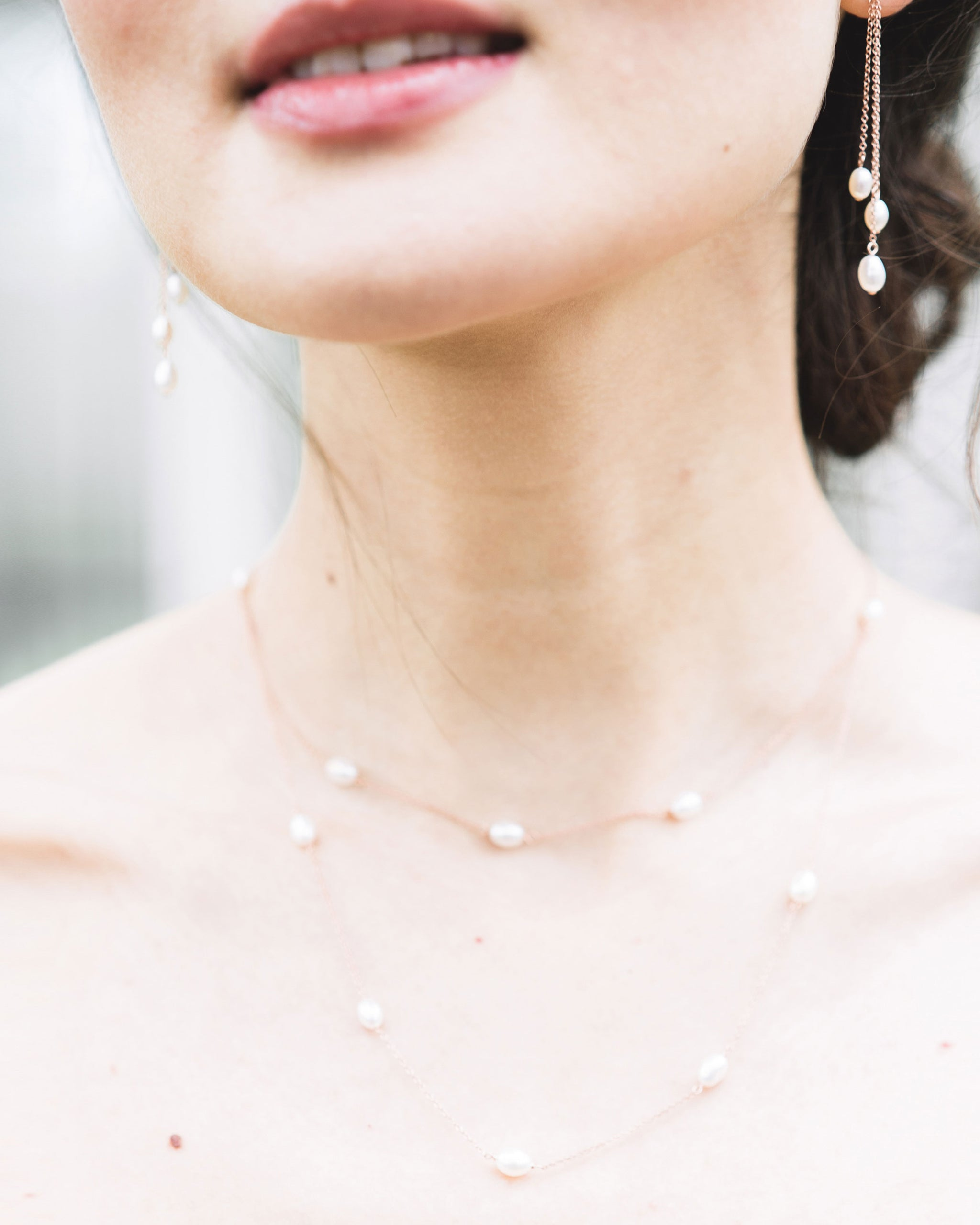 A close-up view of the dainty layered pearl necklace, paired with the dainty pearl trio earrings.