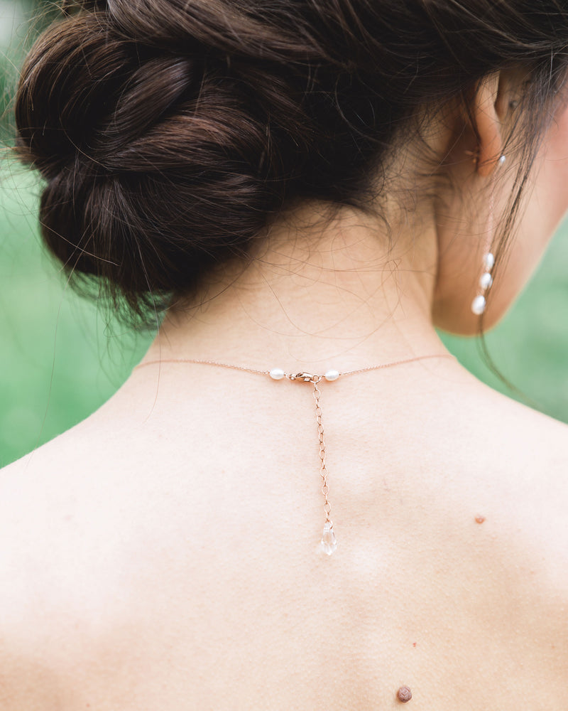 A back view of a model wearing our dainty pearl layered necklace, showing a Swarovski crystal drop and clasp.