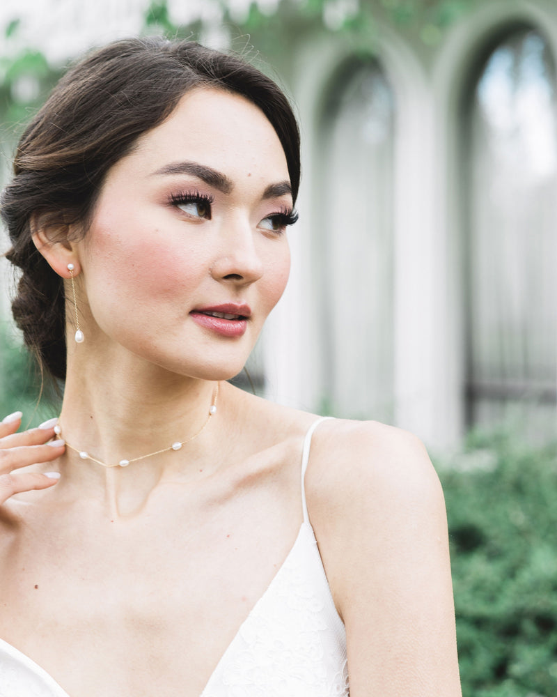 Photograph of the Dainty Pearl Necklace in gold on a model, paired with the Teardrop Pearl Long Earrings.