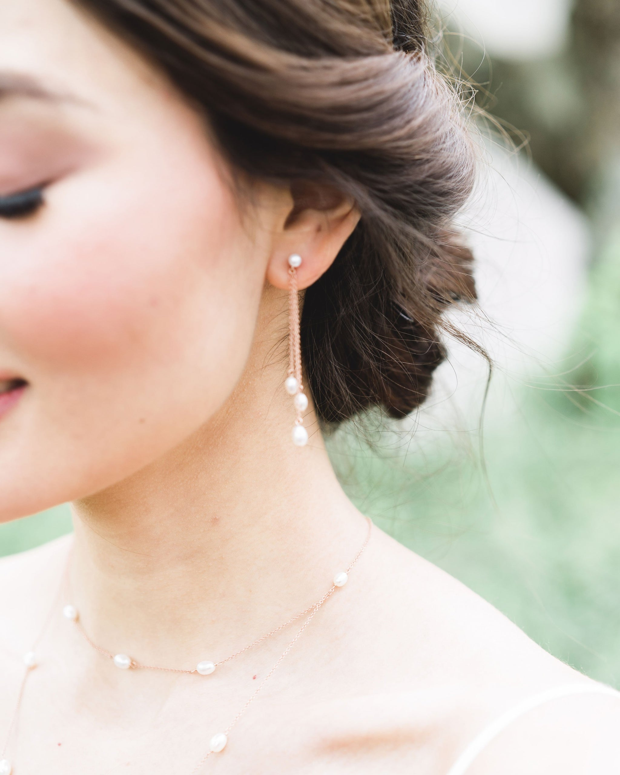 Close up on model of the Dainty Pearl Trio Earrings, paired with the Dainty Pearl Layered Necklace