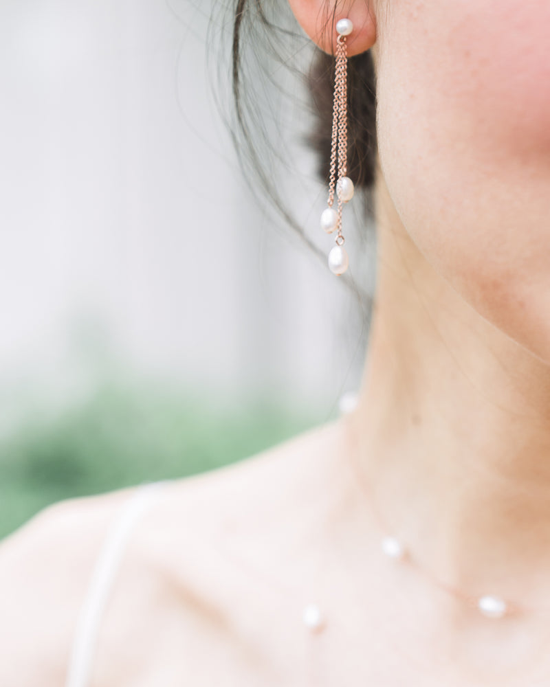 Close up on model of the Dainty Pearl Trio Earrings, paired with the Dainty Pearl Layered Necklace.