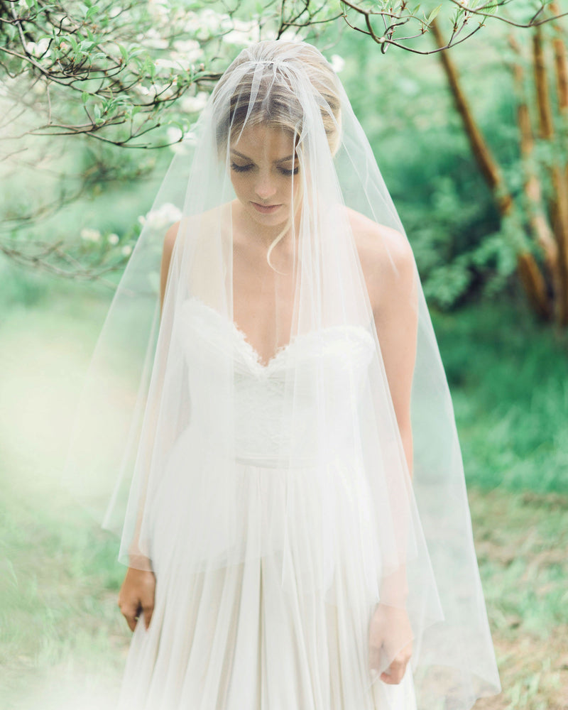 Model wearing circular cut illusion tulle fingertip veil with soft gathers
