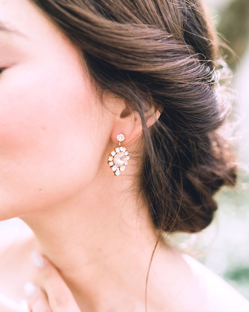 model wearing enchanted swarovski crystal drop earrings in gold with blush stud