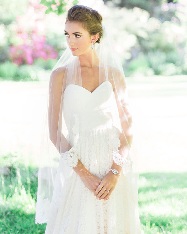 Model wearing illusion tulle lace bridal veil with wide Alencon lace scallop
