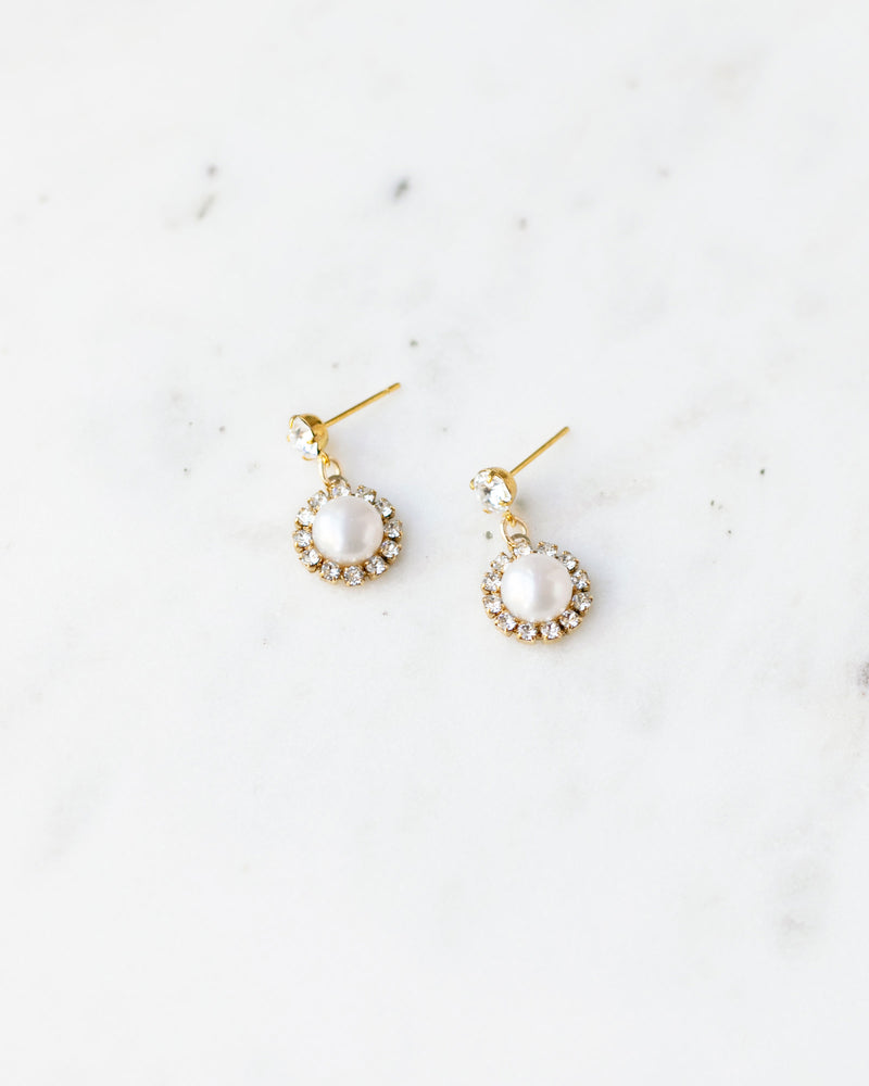 Flatlay photo of the Halo Pearl Drop Bridal Earrings in gold with freshwater pearl.