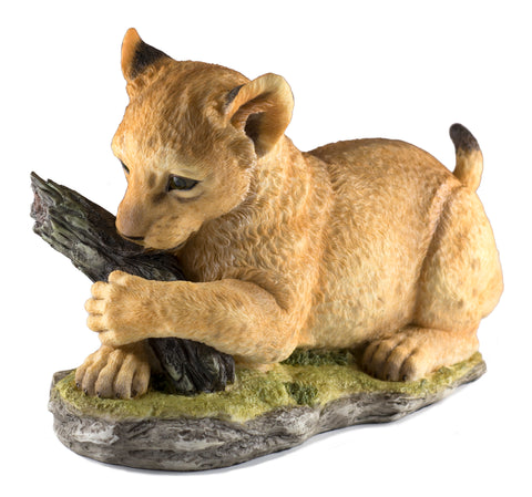Lion cub playing with log figurine